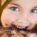Little girl eating ribs